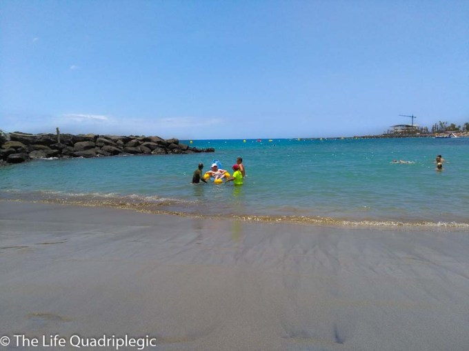 A man sat in a floating beach chair in the shallow Sea close to the beach