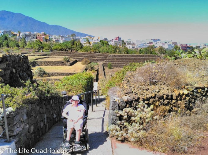 A male wheelchair users that at the top of a sloping pathway which leads down towards some stepped pyramids.