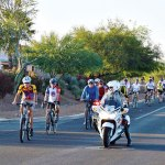 Cyclists head down Abrego escorted by Pima County Sheriff