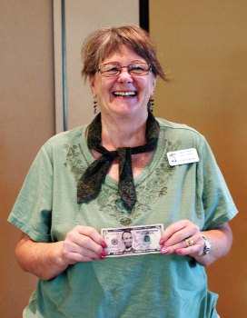 Jan Ederle is all smiles as she holds on tightly to her $5 bill; photo by Sylvia Butler.