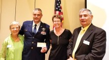 Left to right: MOA Treasurer Peggy McGee presented a check for $2,000 to General MacDonald as Family Readiness Program Manager Barbara Gavre and 1st Vice President for Membership Joe Longo looked on; photo by Betty Atwater