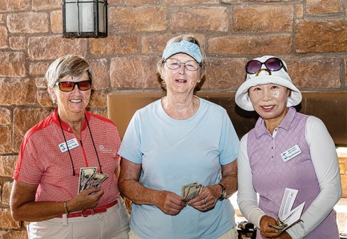 There was a three-way tie between Cathy Thiele (left), Cathy Leary, and Sung Whitehead, with each scoring three holes in one. They each went home with an extra $10 in their pockets. Photo by Jim Burkstrand.