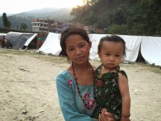 """Kumari Ghale, 20, is from Haku-8 and currently living in Camp 2, Betrawati. She is a single mother of a one-year-old boy. Her husband died after falling from a cliff a year ago. """"I spent the whole year crying,"""" she said. She had been living alone until she was displaced by the quake. All her belongings still lie buried in the debris of her fallen house. She received a cash gift of NPR 10,000 through Nehi Fund to buy some essentials for her herself and her child."""