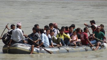 The villagers have to cross the river on a rafting boat to get to the road head