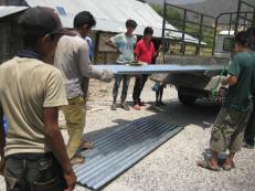 Unloading roofing sheets for the Majhi families of Dhaneghat village, Ramechhap