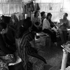 Women group together indoors to talk about a savings and credit scheme.