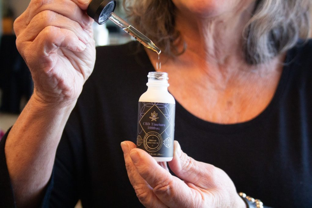 Woman using tincture - Quality CBD - Madison WI
