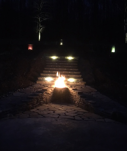 custom stone fire pit lit
