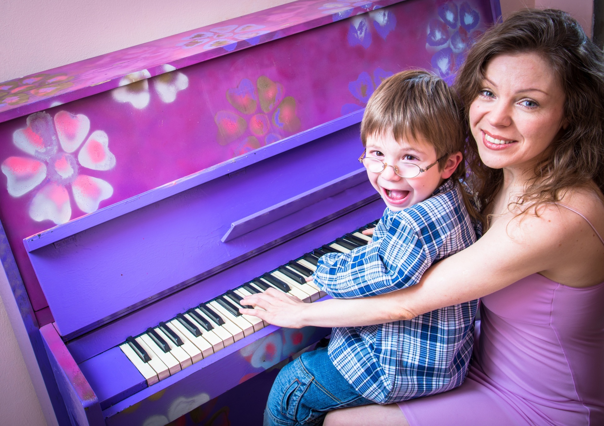 colorful piano being played by mother and son