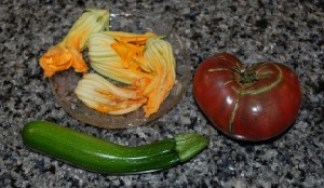 Purple Cherokee heirloom tomato, zucchini squash, and squash blossoms, all grown in my garden last summer (2015). (Photo by Stephanie C. Fox)