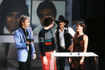 roger-taylor-and-john-deacon-receiving-the-award-for-favourite-pop-single-for-another-one-bites-the-dust-from-barbi-benton-and-johnny-paycheck-american-music-awards-january-1981-2