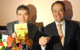 Carlos Velásquez sosteniendo su libro sobre el tequila y en compañía de d