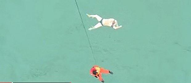 Un rescatista desciende desde un helicóptero al mar en donde flota el cuerpo de un pasajero de la aerolínea AirAsia