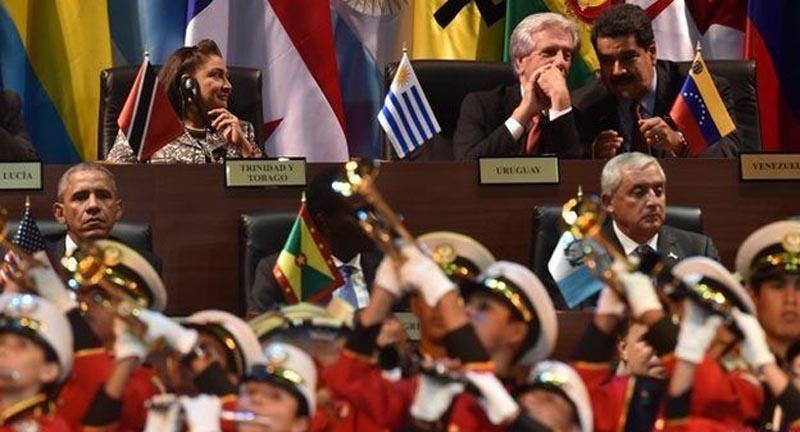 El presidente Obama, a la izquierda, y los presidentes de Uruguay y Venezuela secreteando a la derecha.