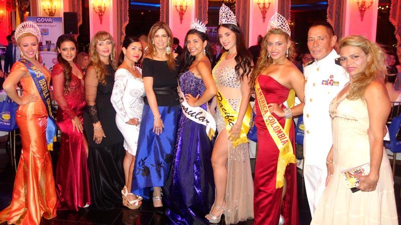 Reinas y personalidades del desfile rodeando a la cónsul María Isabel Nieto, quien está vestida de falda azul.