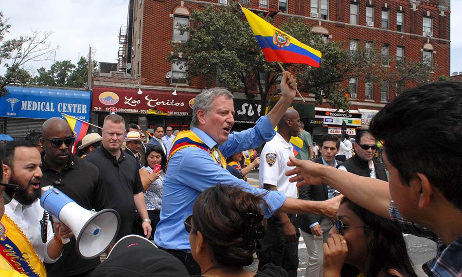 El alcalde Bill de Blasio saludando a los latinos y atr´zas, con altoparlante, el asambleísta Francisco Moya. Foto Humberto Arellano