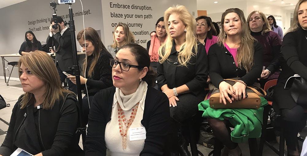 Representantes de la Cámara de Mujeres de Queens escuchando el debate sobre el informe.