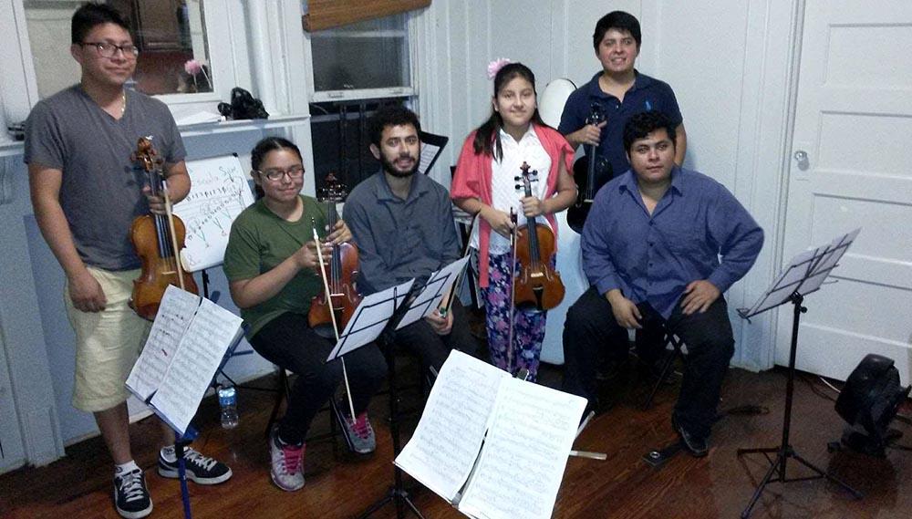 Los músicos de Soloist in America con alumnos.