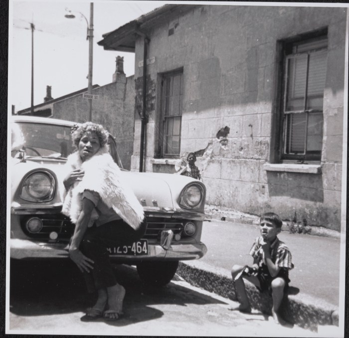 Samantha 'with a floor mat over her as a cape' in Rutgers Street. Neighbour's child, Yusuf (Aysa's son), is watching. Source: Kewpie collection, GALA archive.
