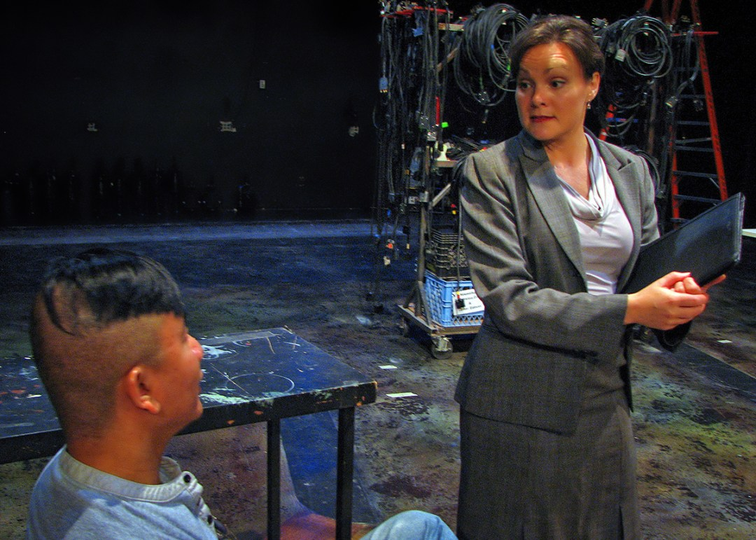 Fabiana Cunningham (Caitlin Frances) interviewing Satan (Ray Tagavilla) in rehearsal for The Last Days of Judas Iscariot.