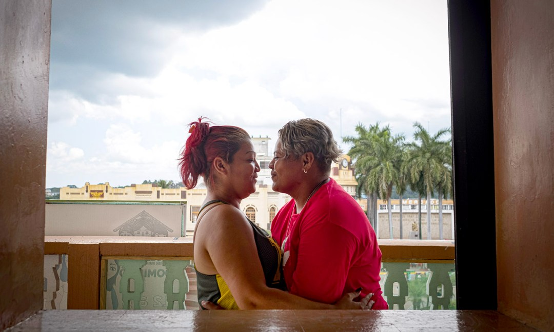 Glenda Diana Cruz, left, and her partner fled San Salvador, El Salvador, after being threatened because of their sexual orientation. Here, they share an intimate moment on the balcony of T'ja Xuj, which overlooks the main plaza in Tapachula