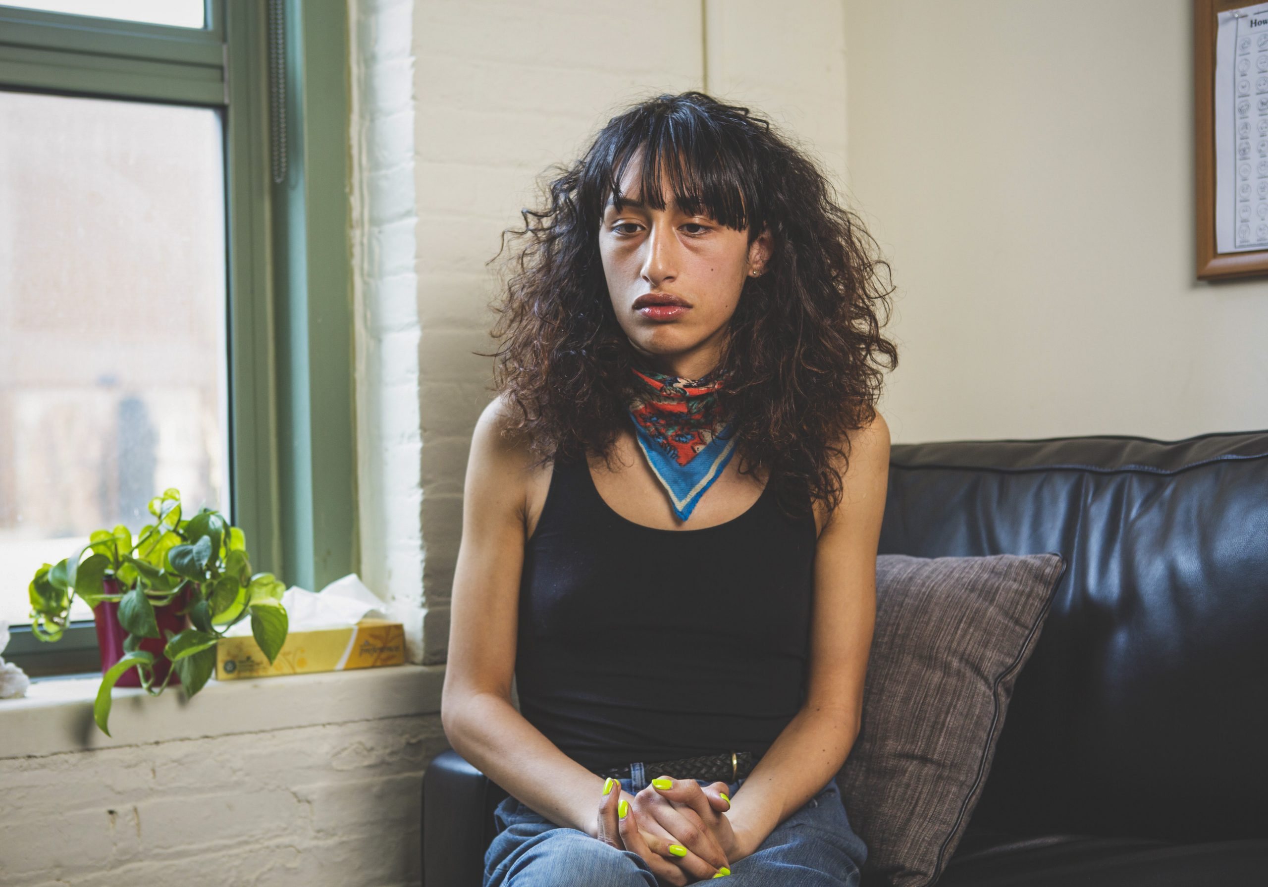 A transgender woman sitting on a therapist's couch and looking upset