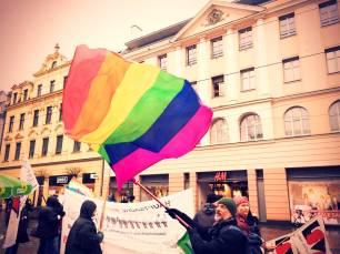 Ein Mann schwenkt eine Regenbogenfahne. Im Hintergrund ist der Infostand der Grünen für Woleranz und Weltoffenheit zusehen.