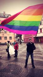 Auf dem Bild schwenkt ein Mann eine Regenbogenfahne