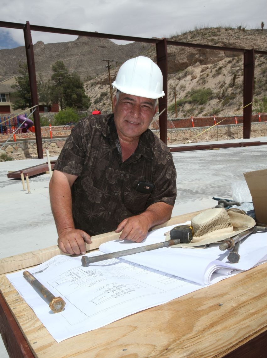 Male owner of construction business stands at work station.