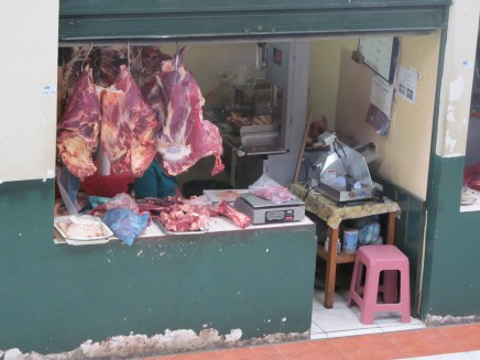 Freshly butchered meat hanging in the mercado at Gualaceo
