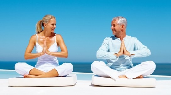 A fit senior couple meditating at the sea shore