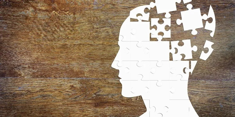 A jigsaw of a persons head with the pieces coming together to form the mind