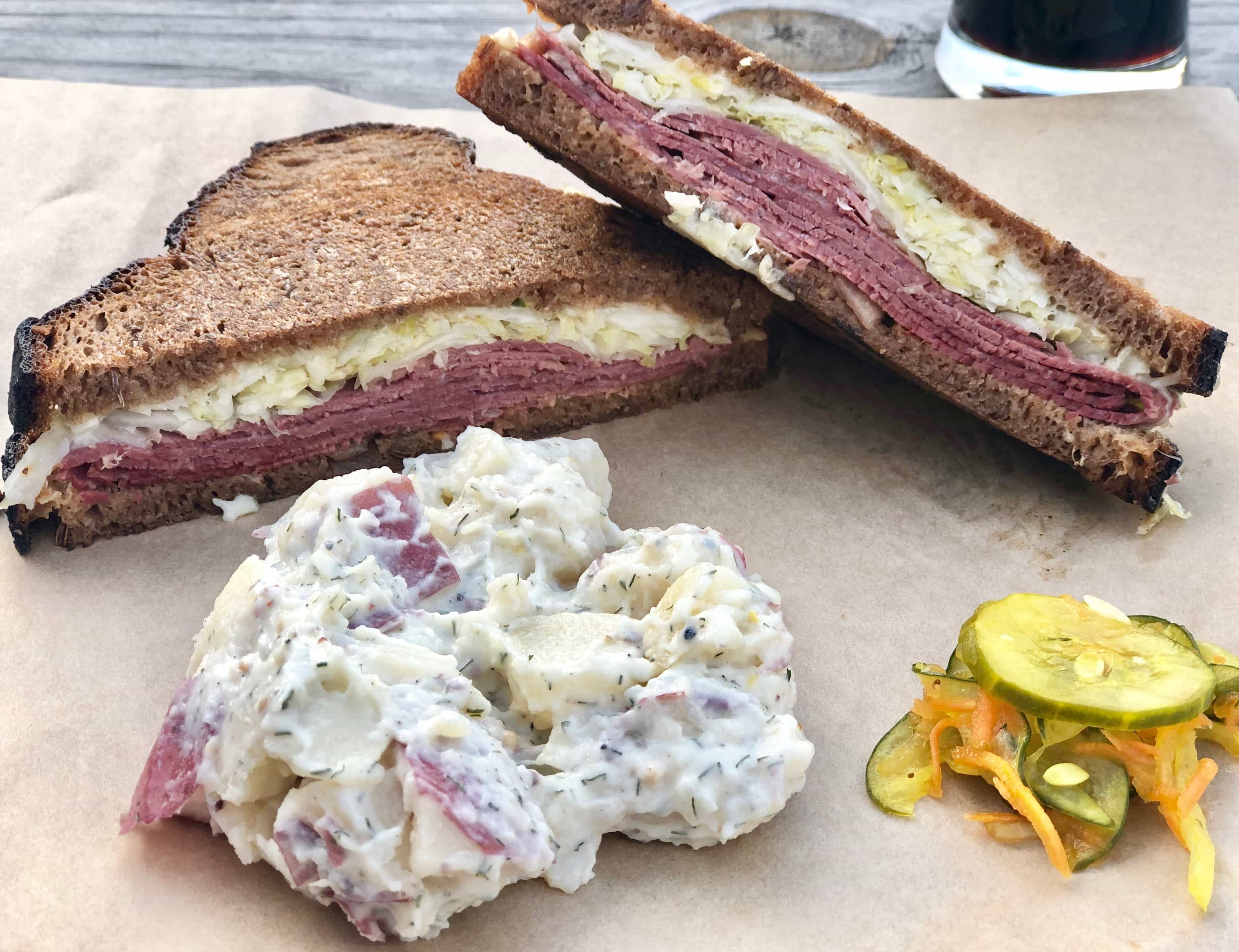 grilled reuben sandwich with a side of potato salad and pickles