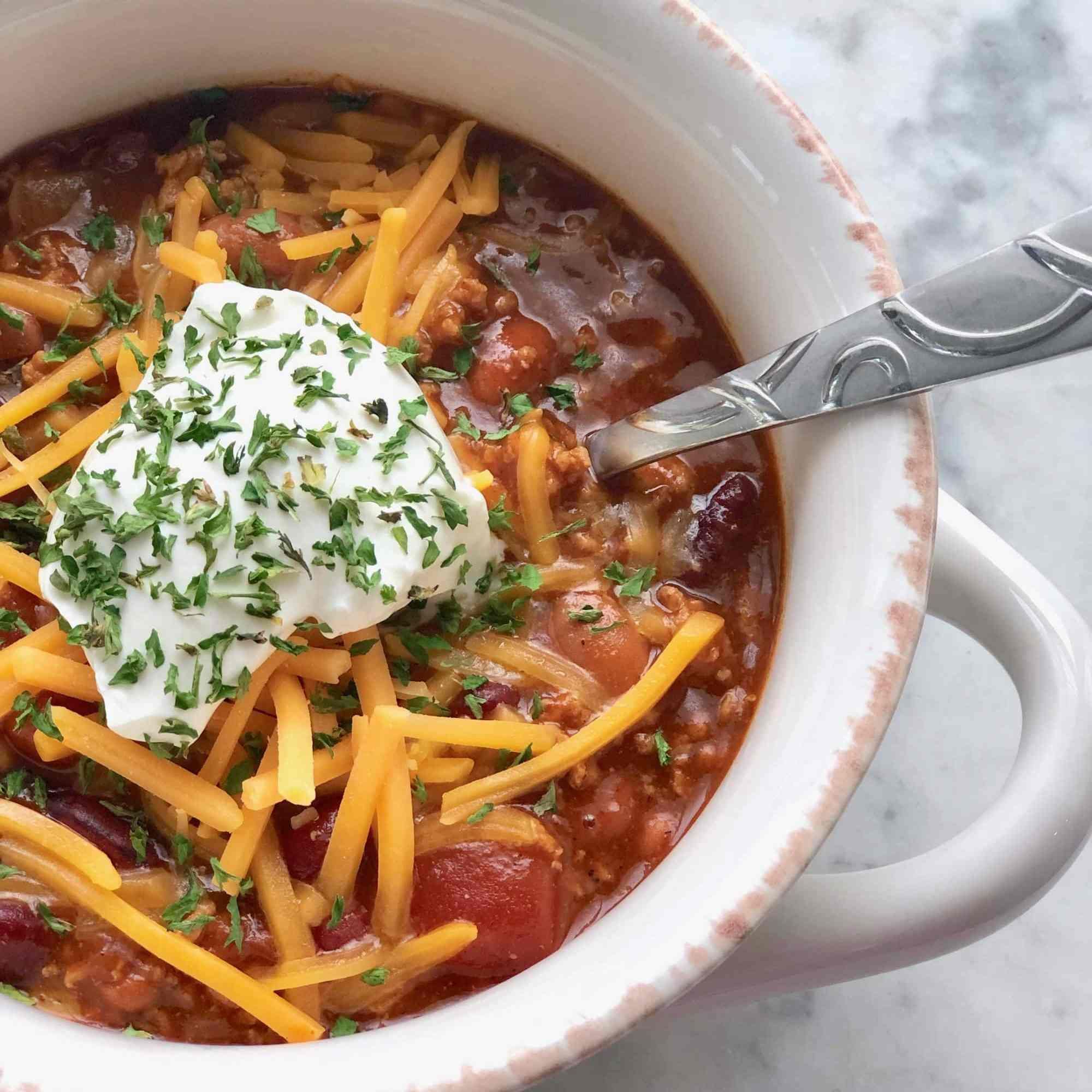 chili in a white bowl with spoon