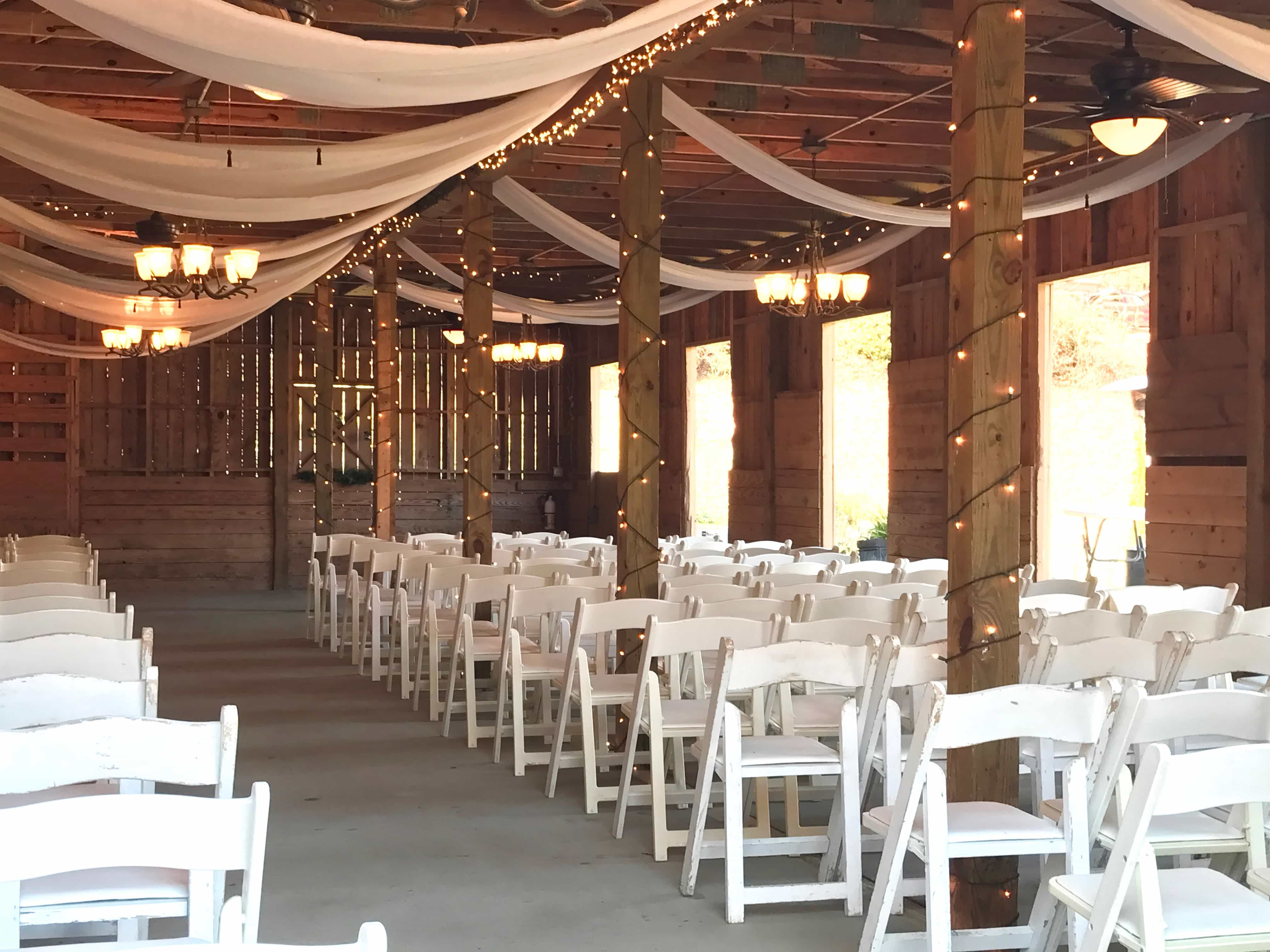 barn with white chairs lined up for a wedding