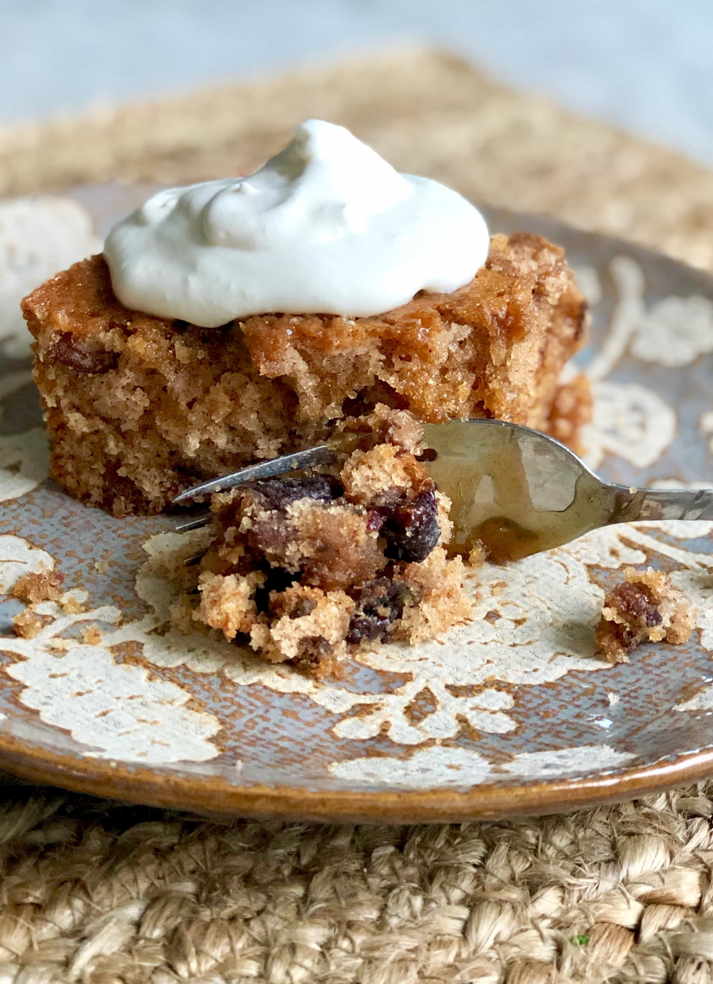 a slice of prune cake with whipped cream on top