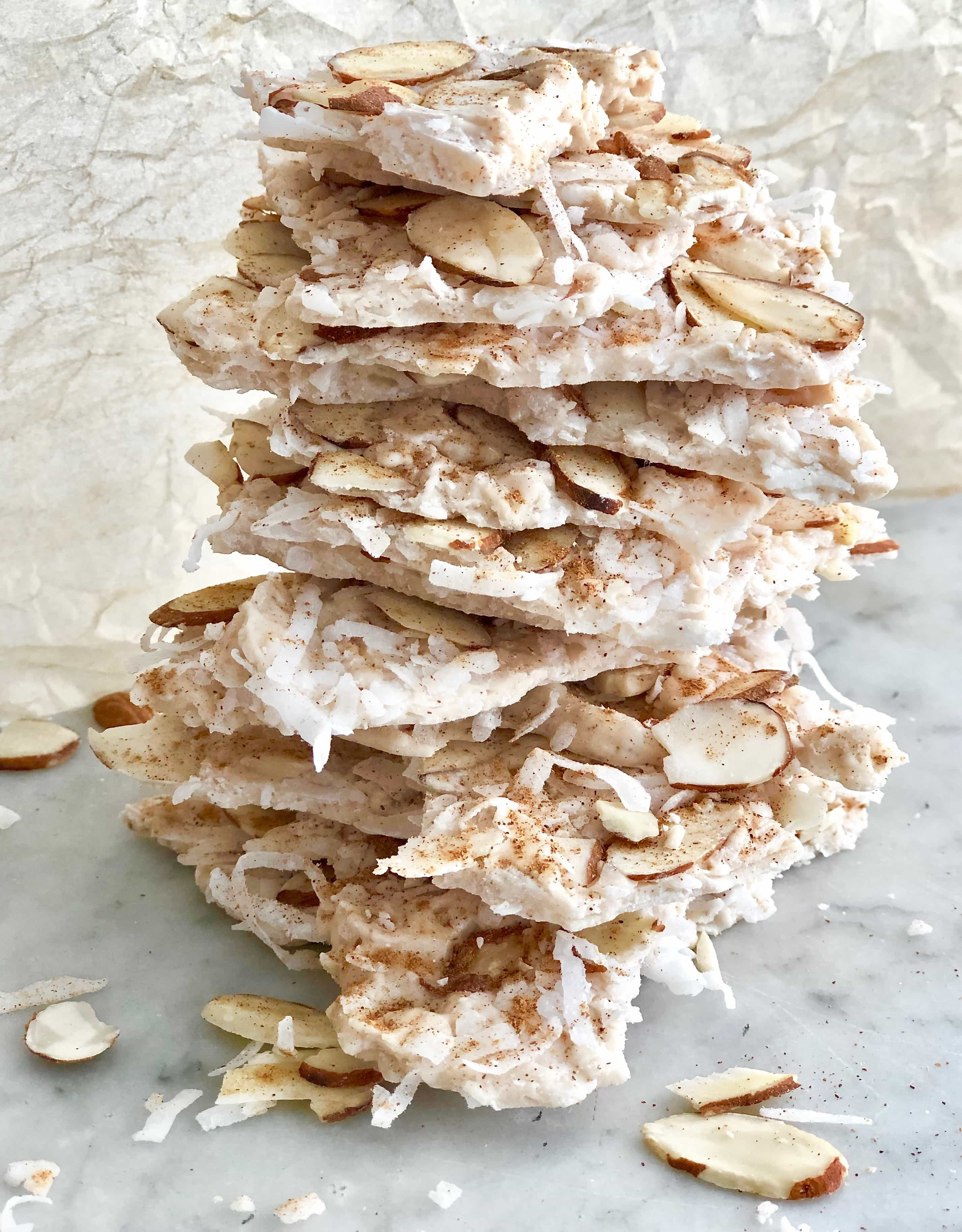 pumpkin spice coconut bark stacked on parchment paper