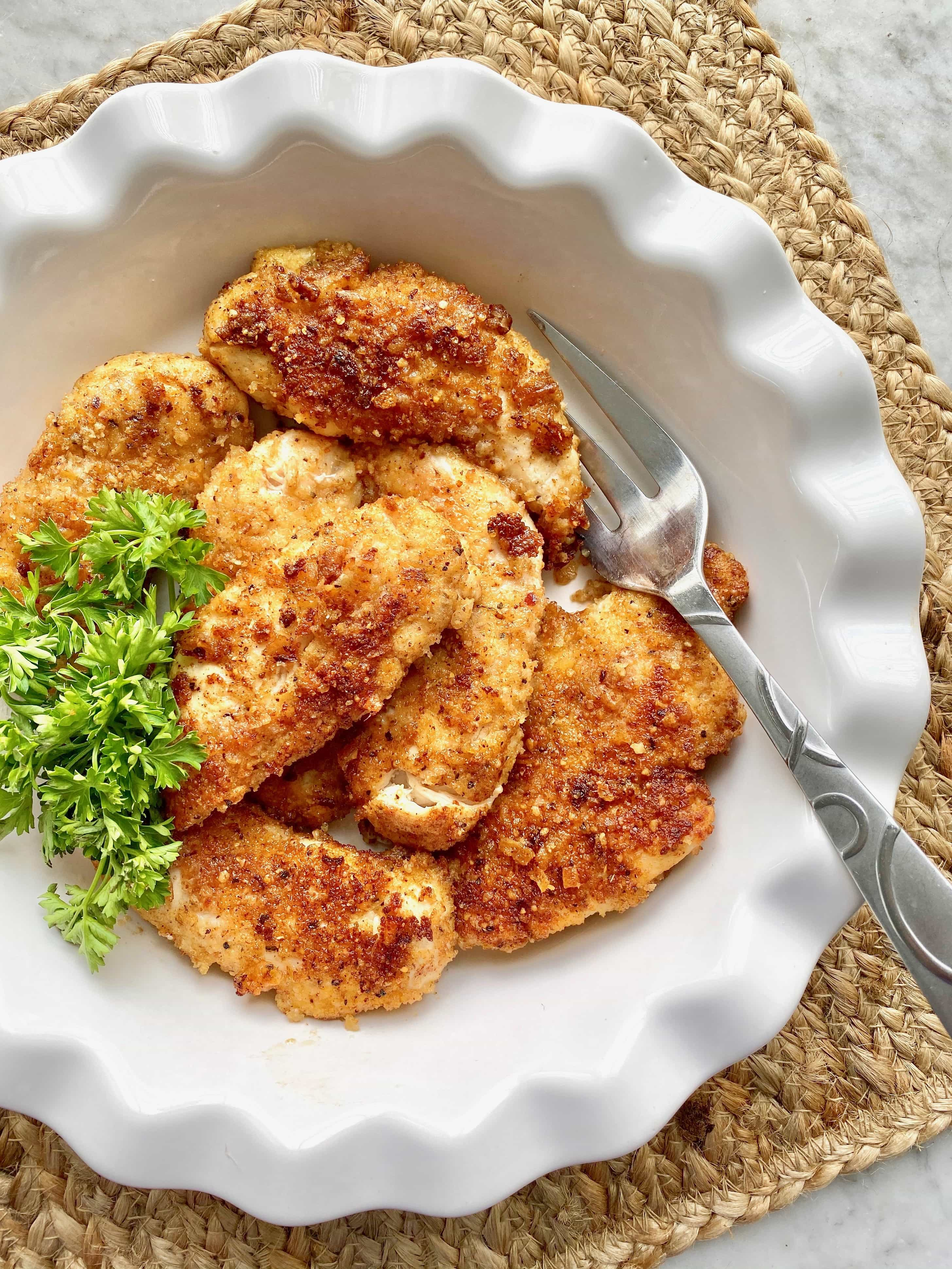 crunchy parmesan chicken in a white dish