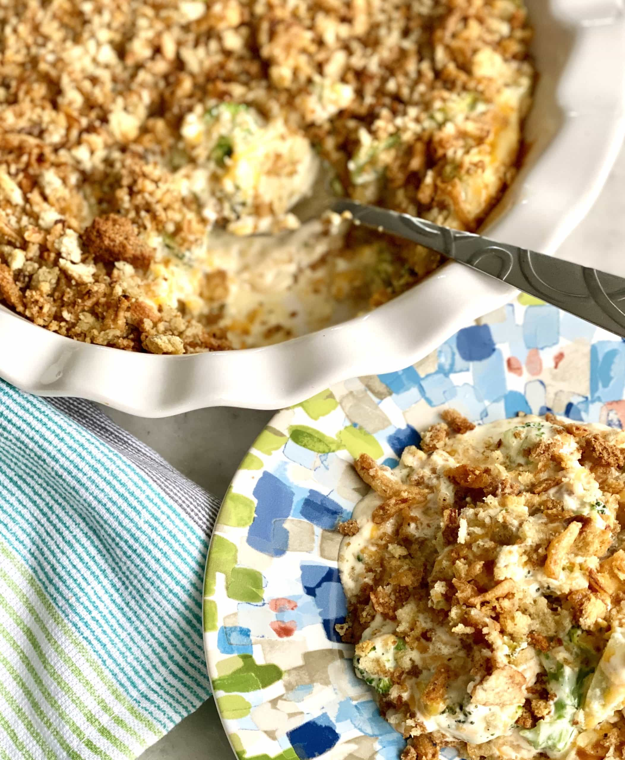 broccoli cheese casserole in a multi colored dish with a spoon