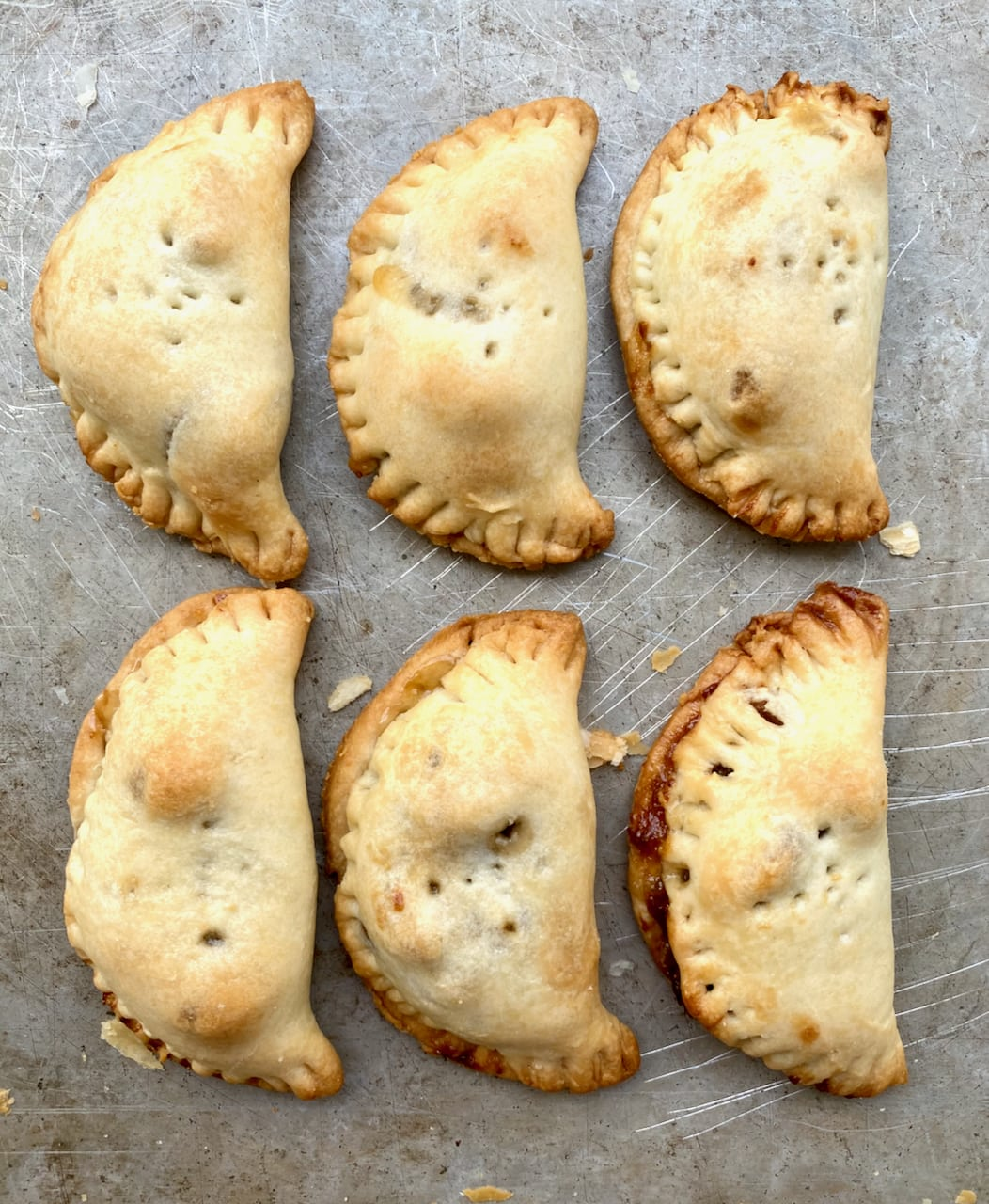 twice baked pecan pie turnovers on a cookie sheet