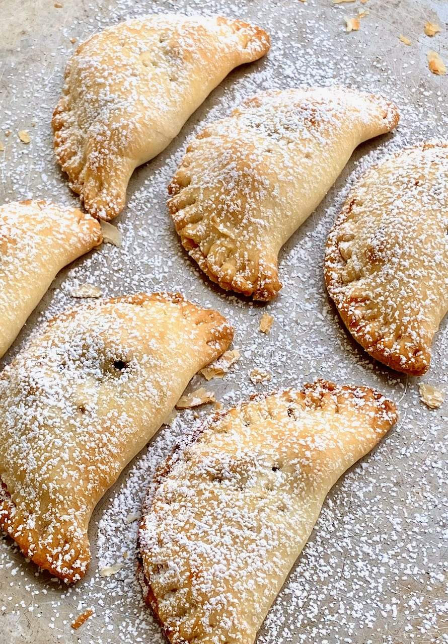 twice baked pecan pie turnovers on a cookie sheet with powdered sugar