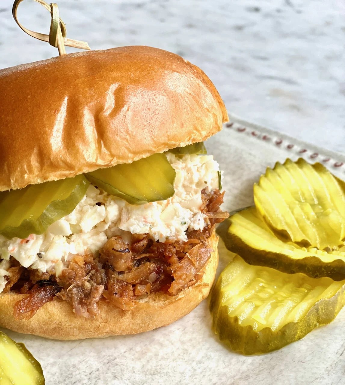 pulled pork barbecue with coleslaw and pickles on a brioche bun