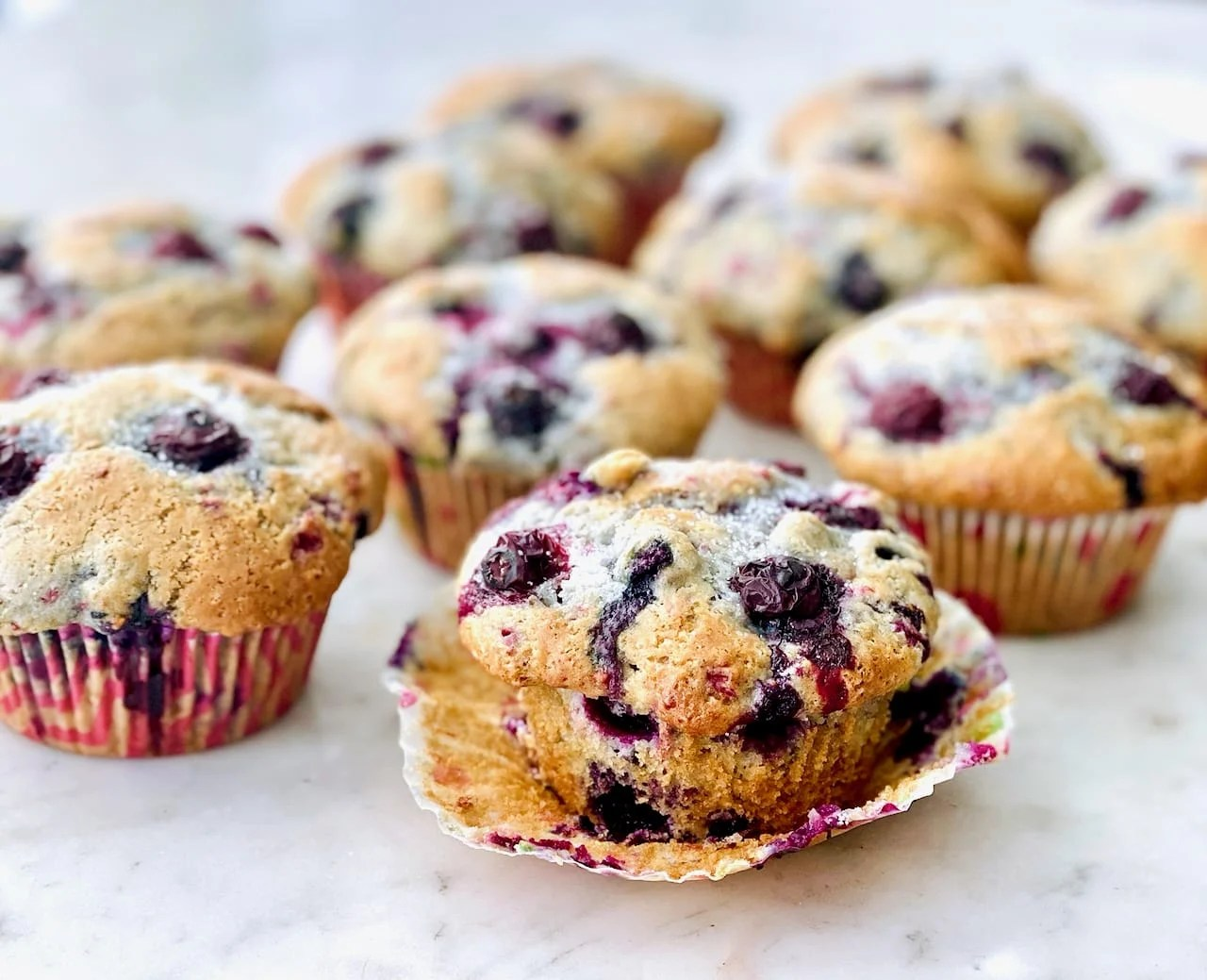 blueberry muffins with one liner pulled down to see the muffin