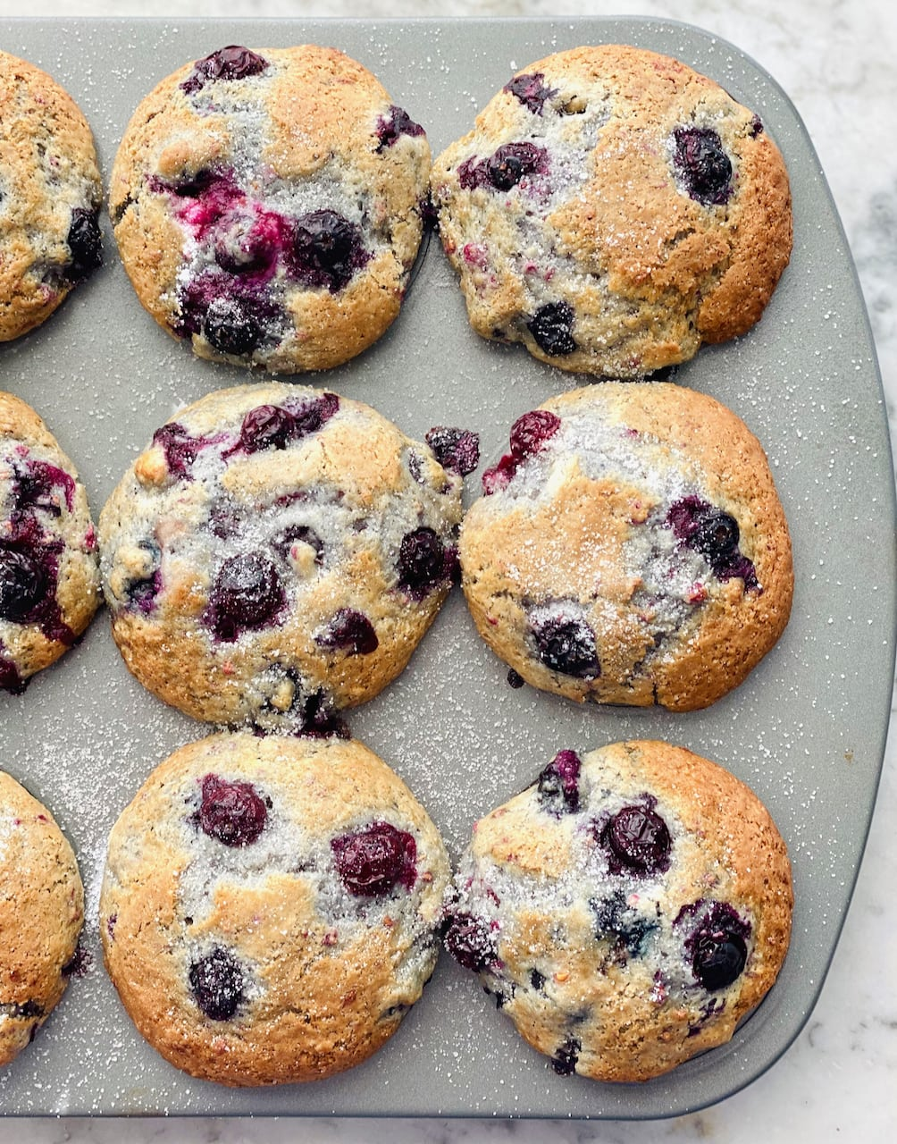 blueberry muffins finished baking in a muffin tin pan