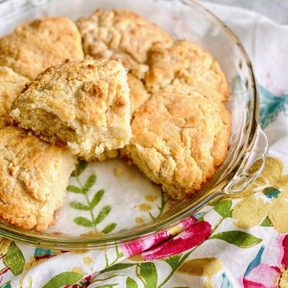 golden brown biscuits in a glass pie plate on a floral napkin
