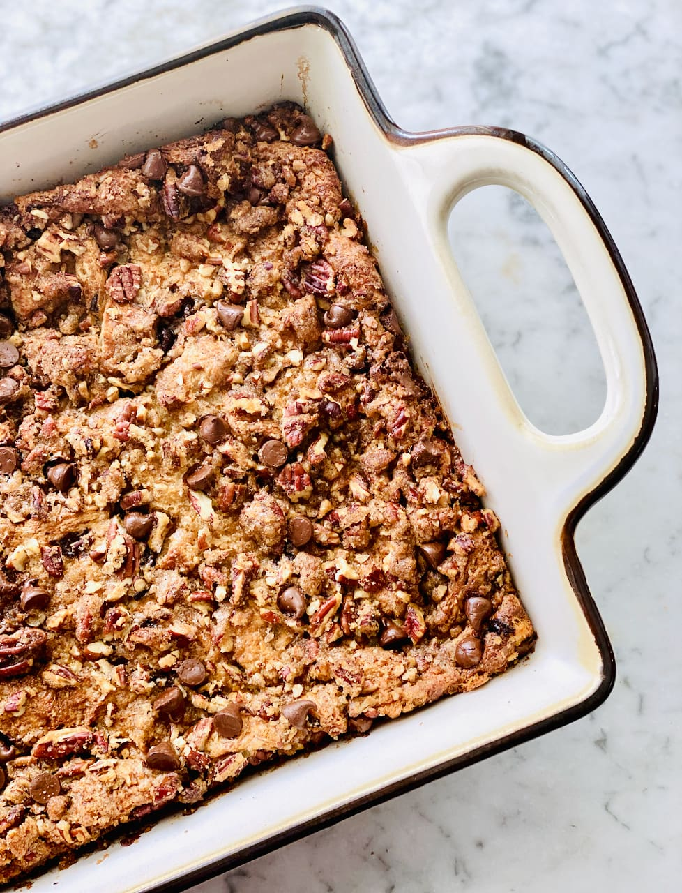 chocolate bread pudding in a white casserole dish with pecans on top