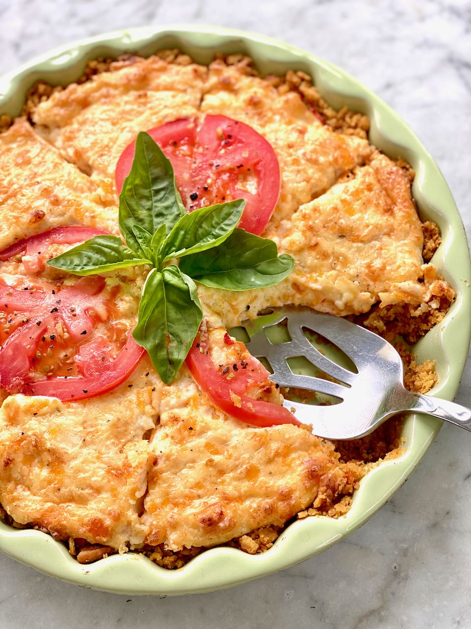 pie server lifting a slice of southern tomato pie with basil and tomatoes on top