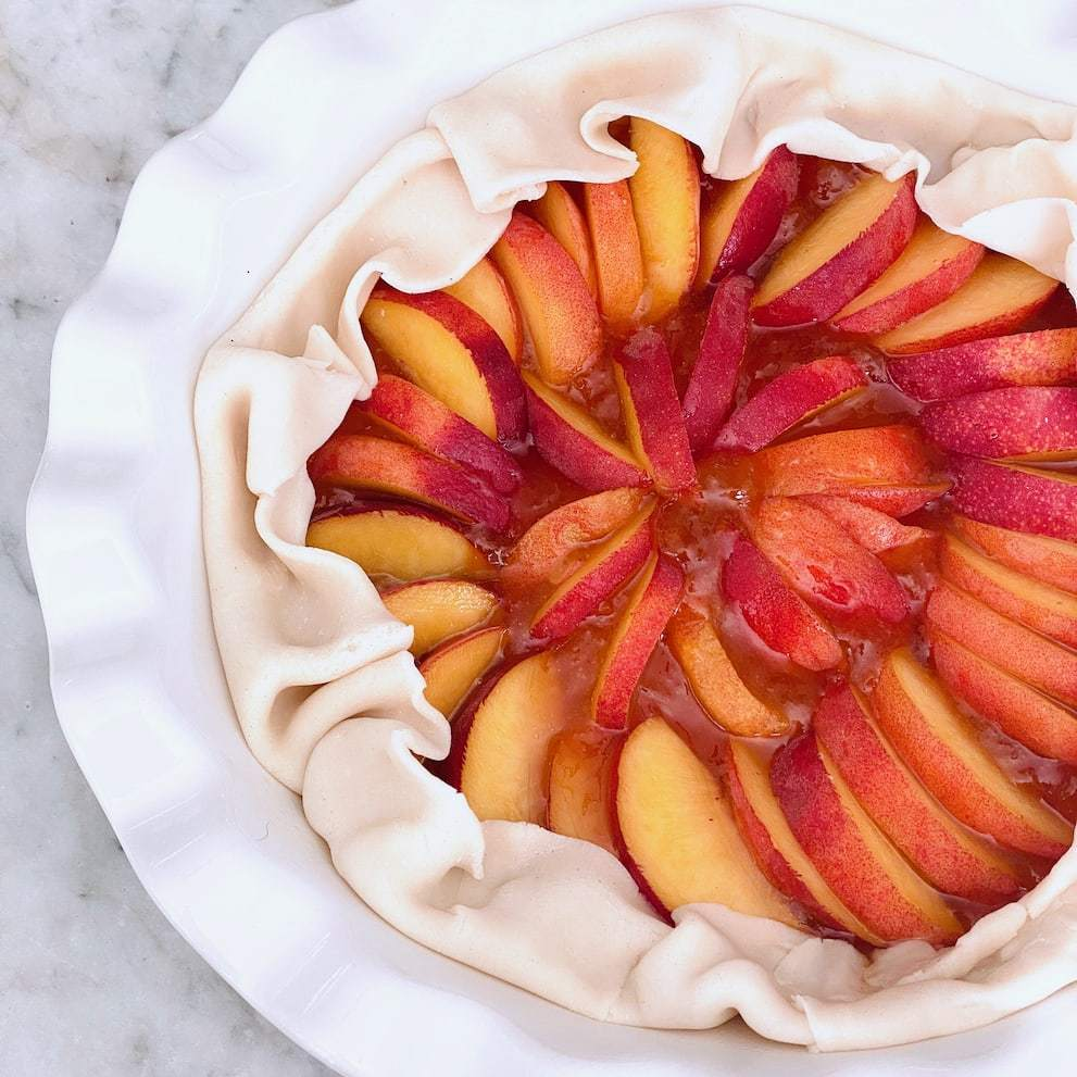 peaches and jam inside a refrigerated pie crust ready to go into the oven