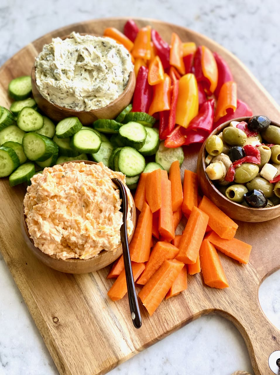 three types of dips with carrots, cucumbers and peppers on a wooden board