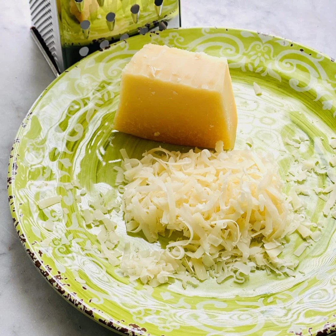 parmesan cheese being shredded by a grater on a green plate